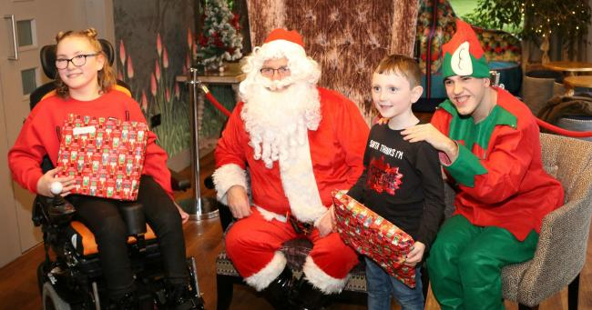 Heidi, 11, from Runcorn with her brother Noah, Santa and elf Aidan during last year's Christmas party for Stick'n'Step