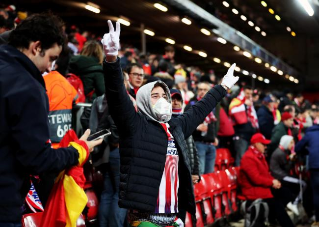 An Atletico Madrid fan wearing a protective mask in the stands to prevent the spread of the coronavirus before the UEFA Champions League round of 16 second leg match at Anfield last night, Wednesday. Picture: Peter Byrne/PA Wire