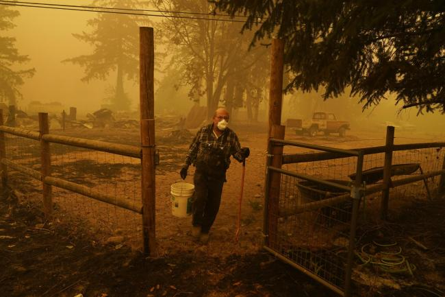 George Coble carries a bucket of water to put out a tree still smouldering on his property destroyed by a wildfire