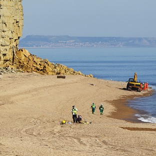 Crews work at the scene of a cliff landslide near Burton Bradstock, Dorset