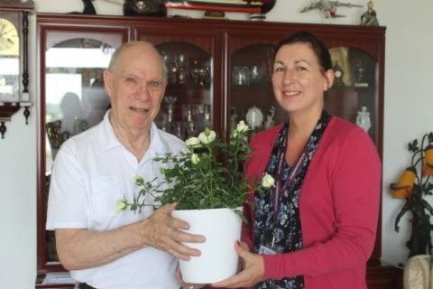 Brian Street receives a gift of roses from Pat Hansen, Halton Housing Trust's housing option manager