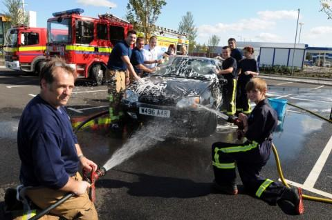 Fire station manager Andy Royle and cadet Sam Robinson wash cars at Tesco