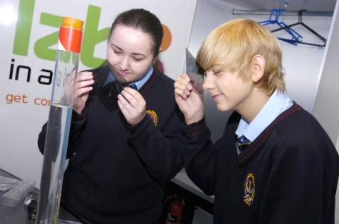 Mollie Stritch and Kai Roberts absorbed in an experiment on board the lab in a lorry