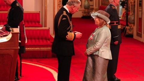 Christine Pugh receiving her MBE from Prince Charles