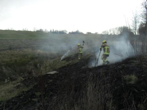 Firefighters tackle a grass fire