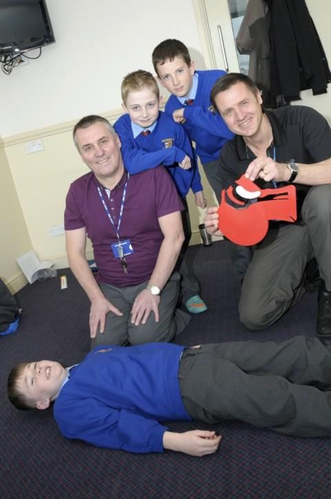 John Smalley plays a victim as resuscitation training officers Stephen McDowell and William Gilhooley, demonstrate first aid with Joshua Smith, and Alex Stanners from Moorfield Primary School