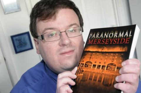 Author Steve Tucker with his book of bizarre stories
