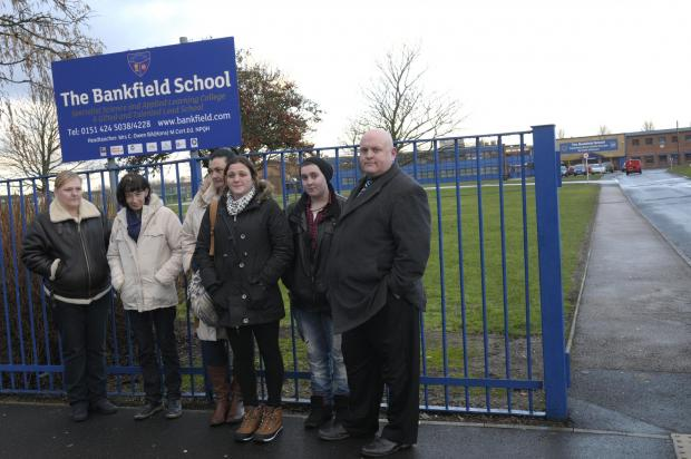 Dad Phil Black (far right) and parents mount a demonstration outside the school