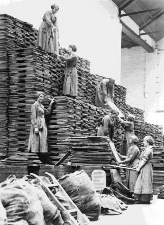 One of the pictures shows women workers stacking oil cakes at an oil and cake factory in Lancashire in 1918