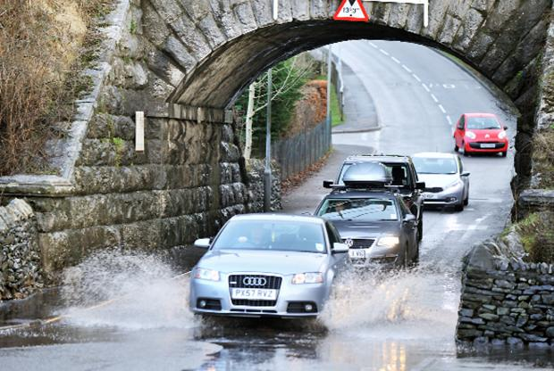 Runcorn and Widnes World: Drivers negotiate the flooding at Parkside Road