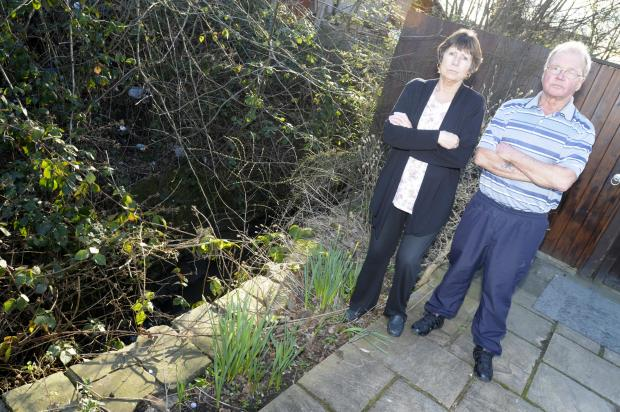 Jackie and Eric Swain beside the contaminated brook in their garden