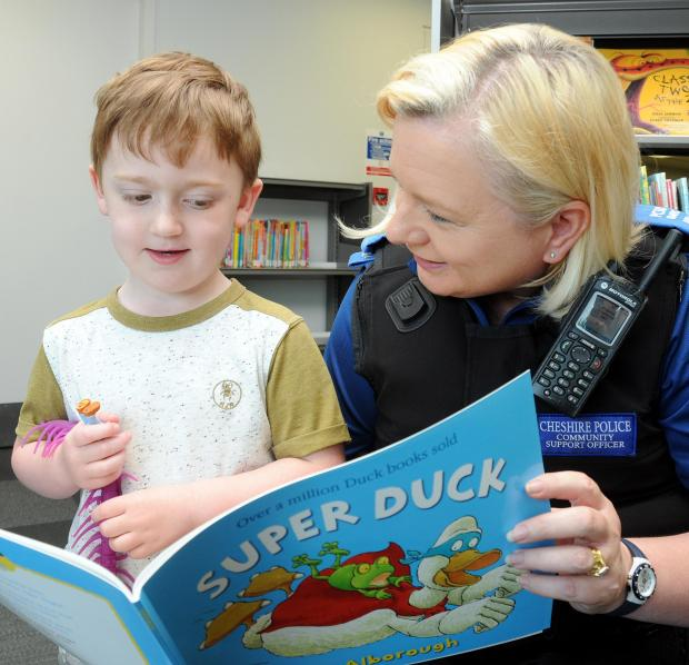 PCSO Lynn Parr reads to Oliver Taylor, aged four