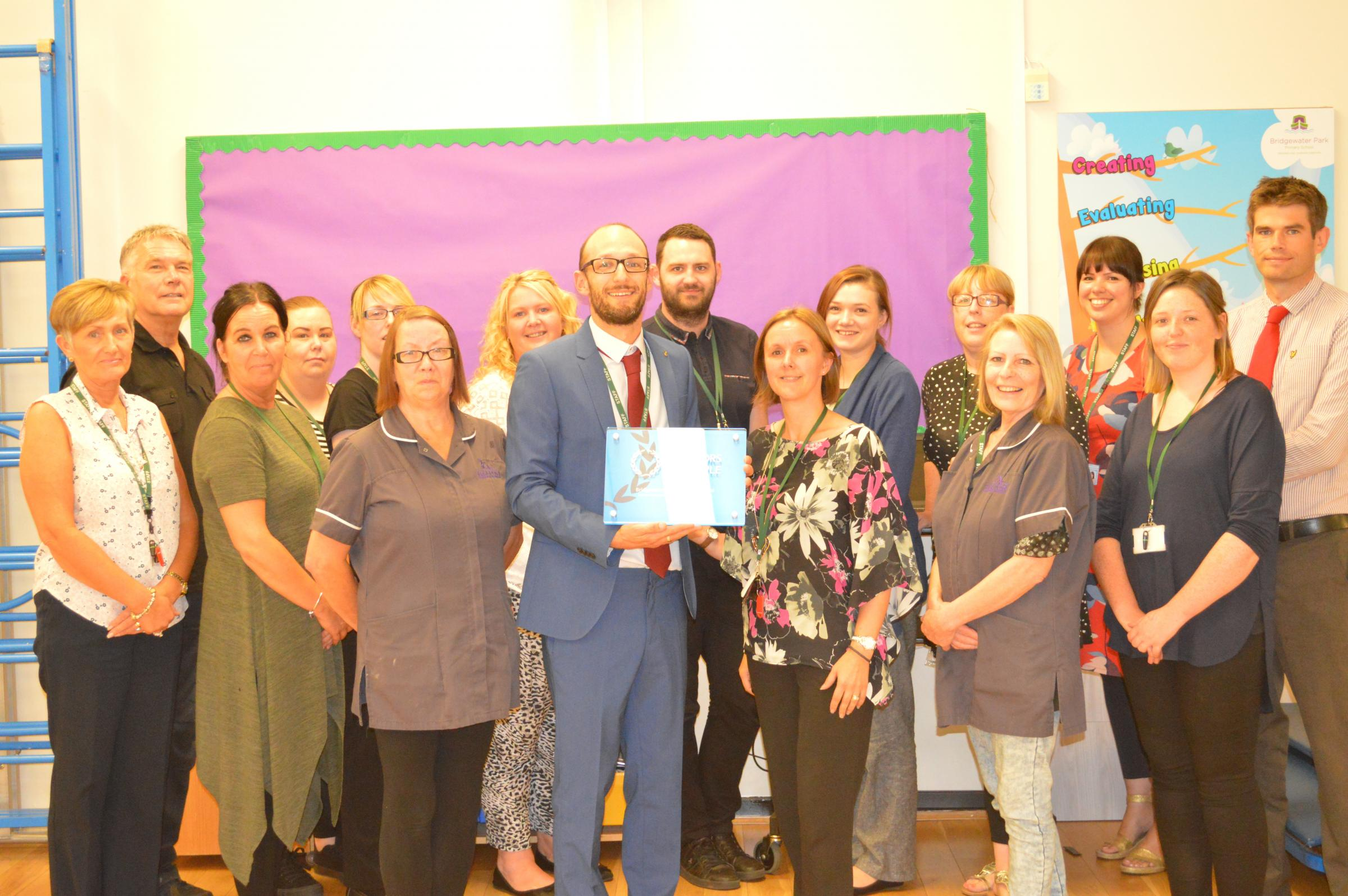 Principal Paul Holloway celebrates achieving Investors in People with staff at Bridgewater Park Primary School
