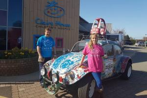 Heather and Colin Maddox with Betty, their 1971 VW Beetle, outside Claire House Children's Hospice
