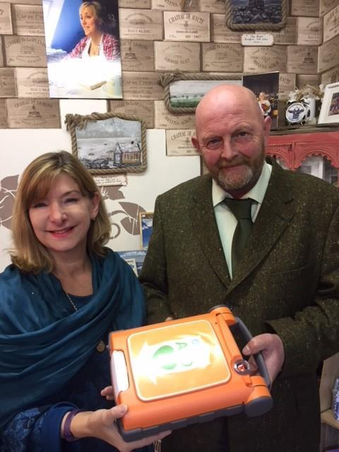 Have a Heart Foundation founder Eric Hale presents a defibrillator to Anne Hignell of Runcorn Rowing Club