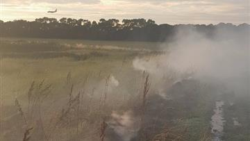 Firefighters spent almost three hours tackling a big grass fire on the banks of the River Mersey in Hale